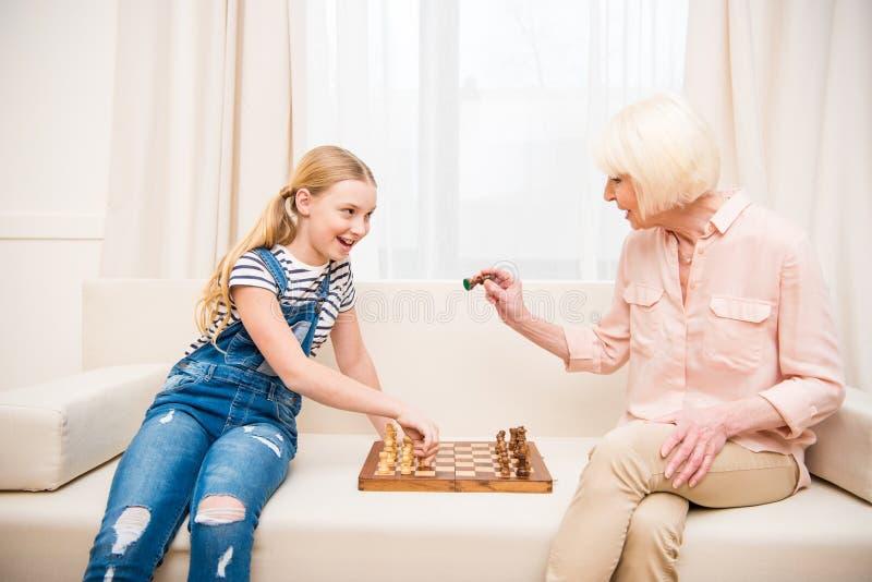 Κορίτσι με τη συνεδρίαση γιαγιάδων στον καναπέ και το σκάκι παιχνιδιού στοκ φωτογραφίες