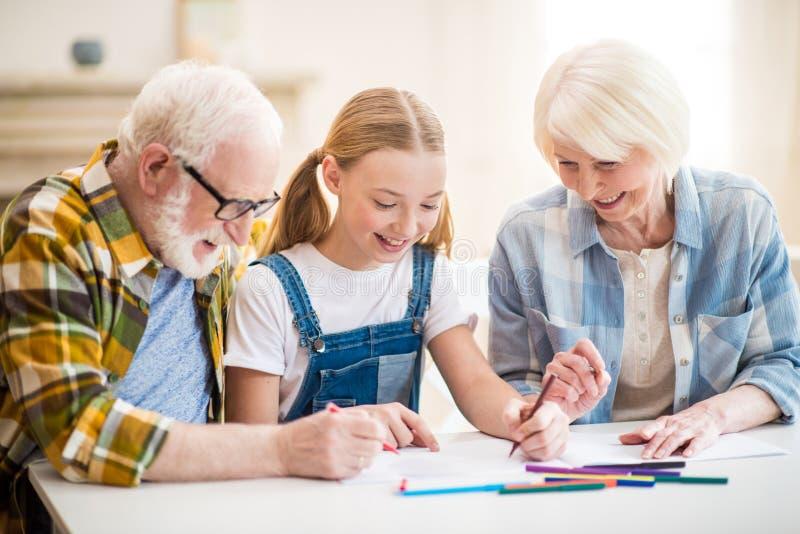 Κορίτσι με τη συνεδρίαση παππούδων και γιαγιάδων στον πίνακα και το σχεδιασμό από κοινού στοκ εικόνες