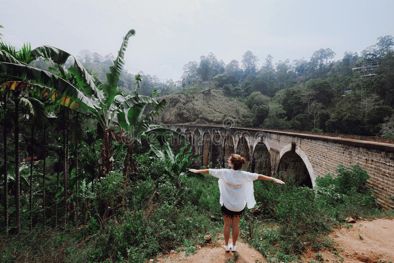 Κορίτσι με τις ανοικτές στάσεις όπλων ενάντια στη γέφυρα στοκ φωτογραφία με δικαίωμα ελεύθερης χρήσης