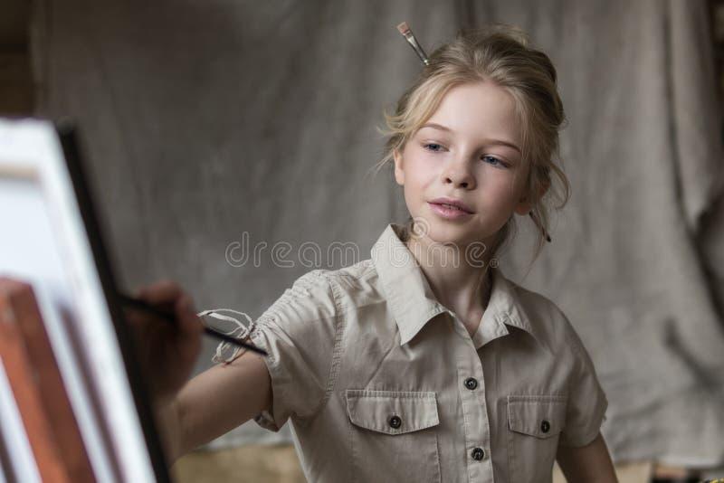 Κορίτσι με τις βούρτσες κοντά easel με την εικόνα των λουλουδιών στο εσωτερικό στοκ εικόνα με δικαίωμα ελεύθερης χρήσης