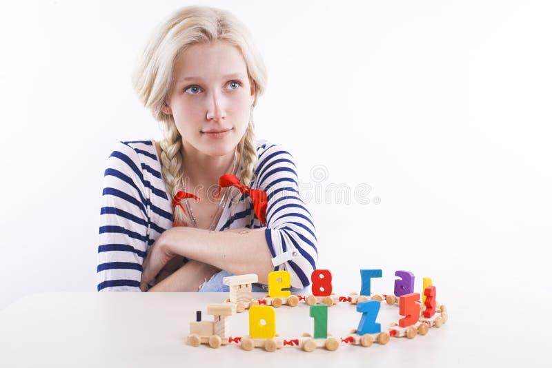 Κορίτσι με τις πλεξίδες και το ξύλινο παιχνίδι στοκ φωτογραφία