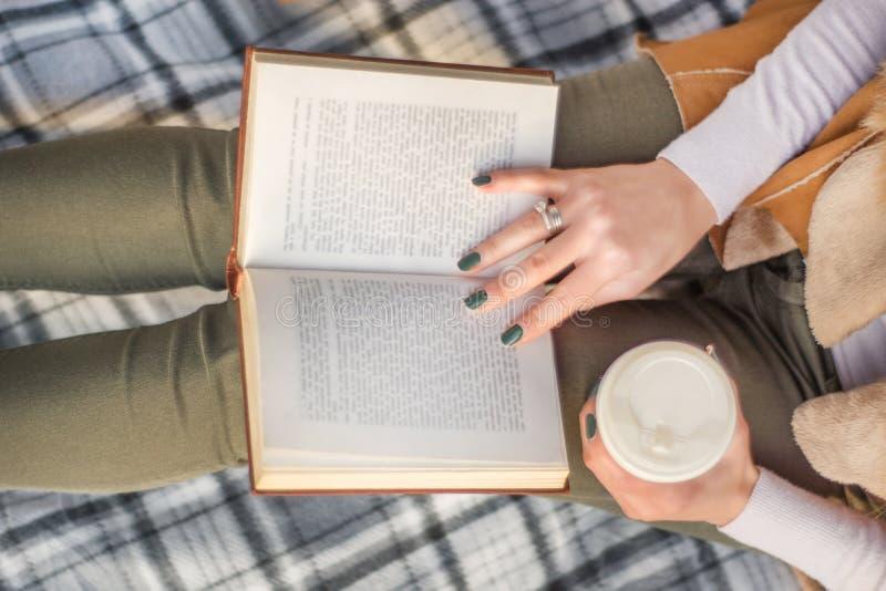 Κορίτσι με το βιβλίο στα πόδια και τον καφέ υπό εξέταση στοκ φωτογραφία με δικαίωμα ελεύθερης χρήσης