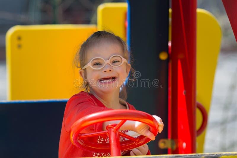 Κορίτσι με το κάτω σύνδρομο που έχει τη διασκέδαση στην παιδική χαρά στοκ εικόνες με δικαίωμα ελεύθερης χρήσης