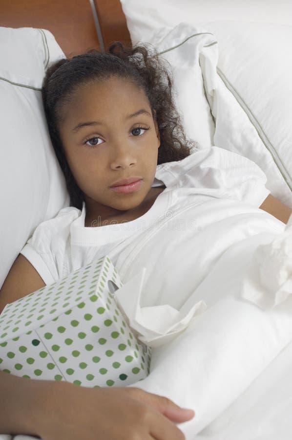 Κορίτσι με το κιβώτιο ιστού στο κρεβάτι στοκ εικόνες