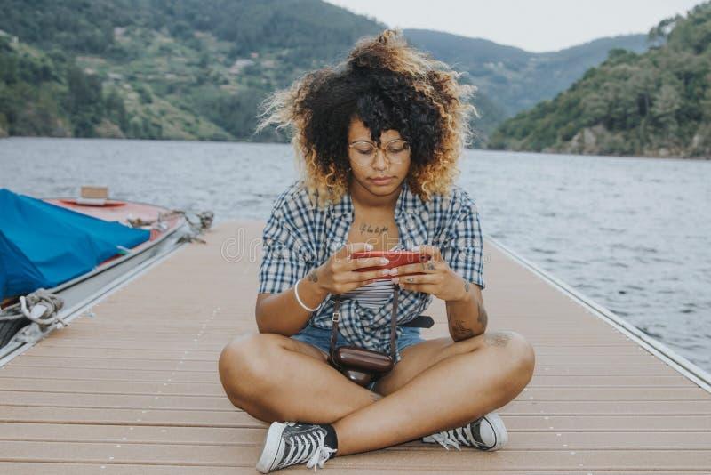 Κορίτσι με το κινητό τηλέφωνο στο λιμενοβραχίονα στοκ φωτογραφία με δικαίωμα ελεύθερης χρήσης
