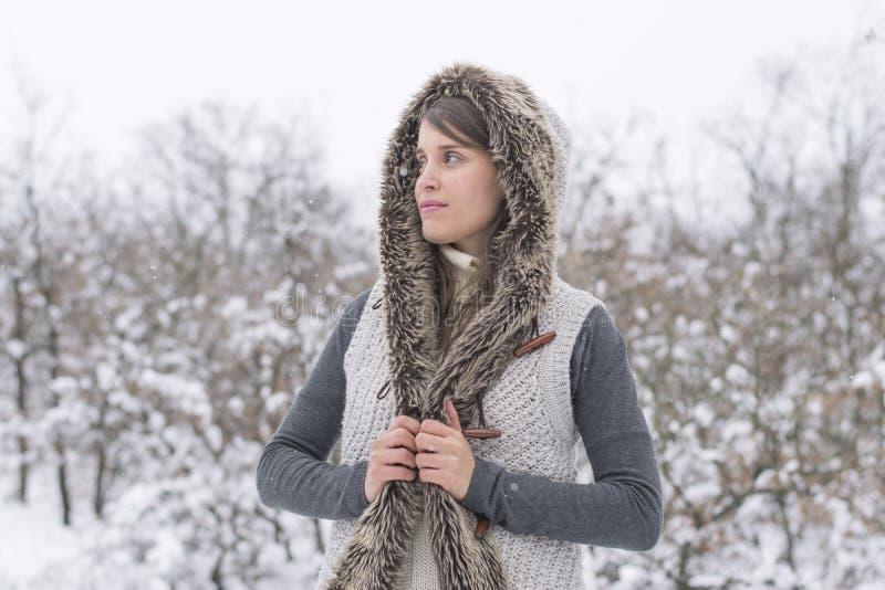Κορίτσι με το με κουκούλα παλτό στο χιόνι στοκ εικόνα με δικαίωμα ελεύθερης χρήσης