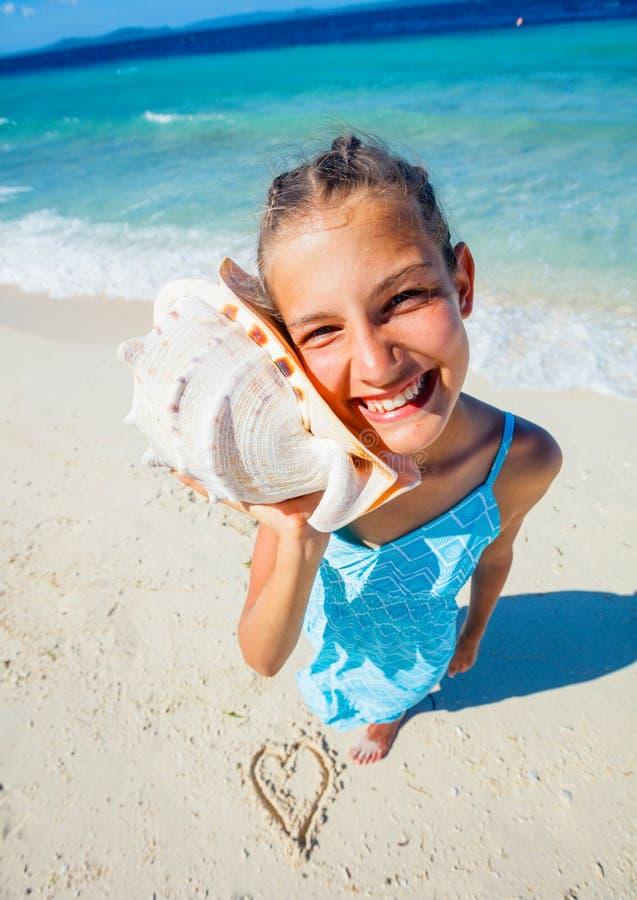 Κορίτσι με το κοχύλι στην παραλία στοκ εικόνες