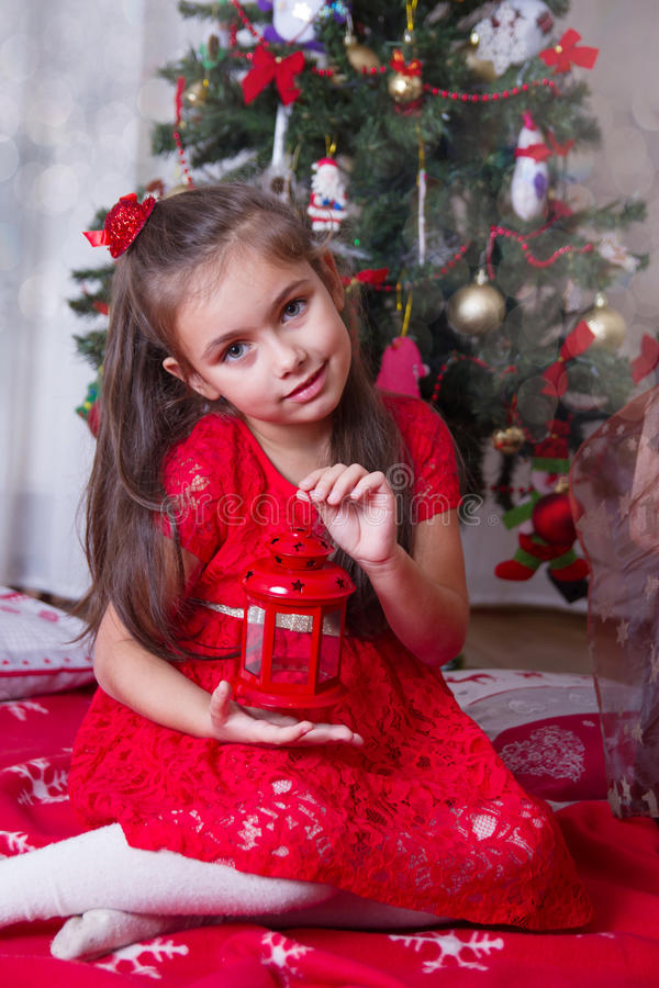 Κορίτσι με το κόκκινο φανάρι κάτω από το χριστουγεννιάτικο δέντρο στοκ φωτογραφία