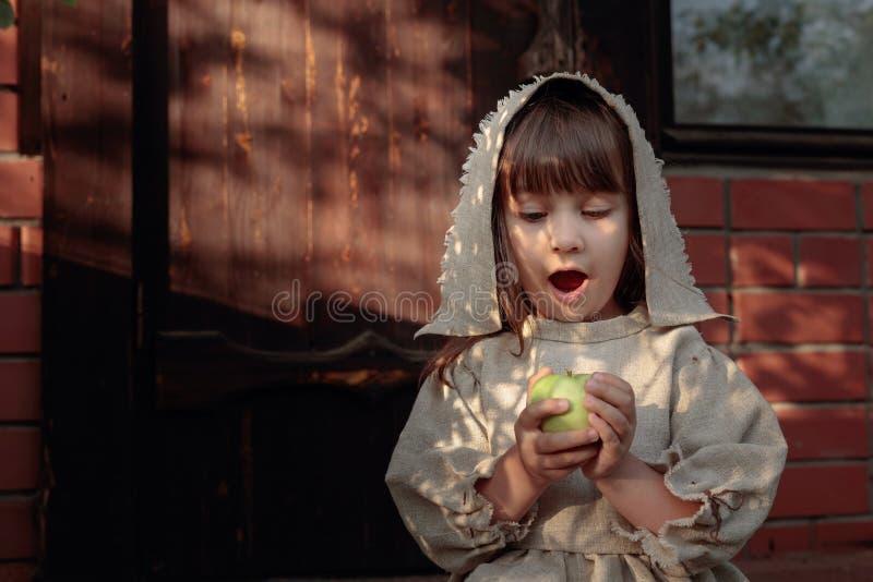Κορίτσι με το μήλο σε ένα θερινό βράδυ κοντά στο παλαιό σπίτι στοκ φωτογραφίες με δικαίωμα ελεύθερης χρήσης