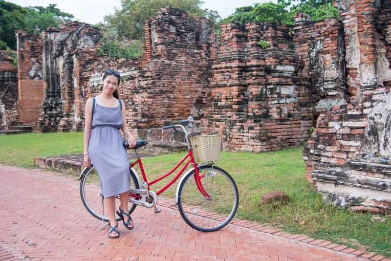 Κορίτσι με το ποδήλατο στις μπροστινές αρχαίες καταστροφές Ayutthaya, Ταϊλάνδη στοκ εικόνες