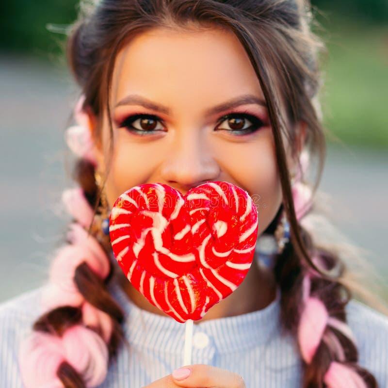 Κορίτσι με το lollipop Πρότυπη γυναίκα γοητείας ομορφιάς με την καθιερώνουσα τη μόδα τρίχα που κρατά τη ρόδινη γλυκιά ζωηρόχρωμη  στοκ εικόνες