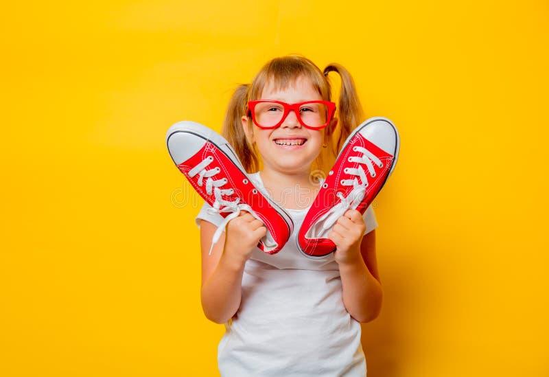 Κορίτσι μικρών παιδιών στα γυαλιά με τα gumshoes στοκ εικόνες