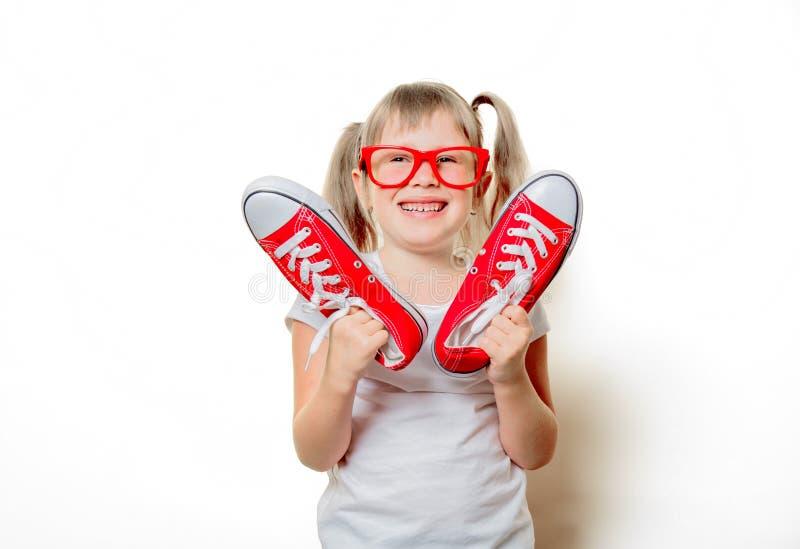Κορίτσι μικρών παιδιών στα γυαλιά με τα gumshoes στοκ φωτογραφία
