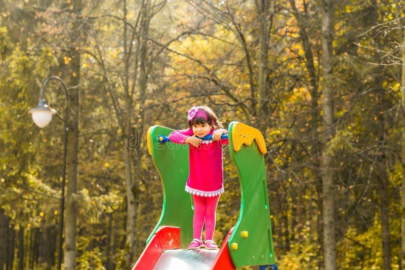 Κορίτσι μικρών παιδιών που έχει τη διασκέδαση στην παιδική χαρά μια ημέρα φθινοπώρου στοκ φωτογραφίες με δικαίωμα ελεύθερης χρήσης