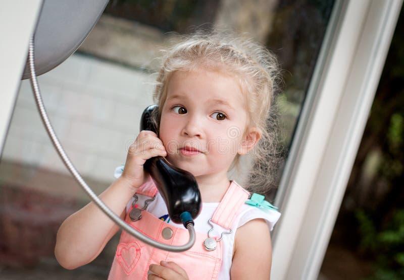 Κορίτσι μικρών παιδιών που μιλά με το τηλέφωνο πόλεων στοκ φωτογραφία