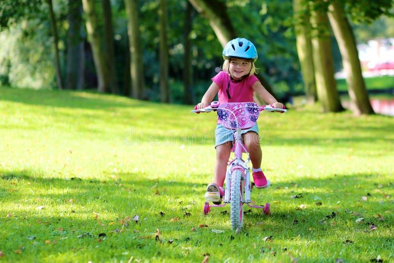 Κορίτσι μικρών παιδιών που οδηγά το ποδήλατό της στοκ εικόνα