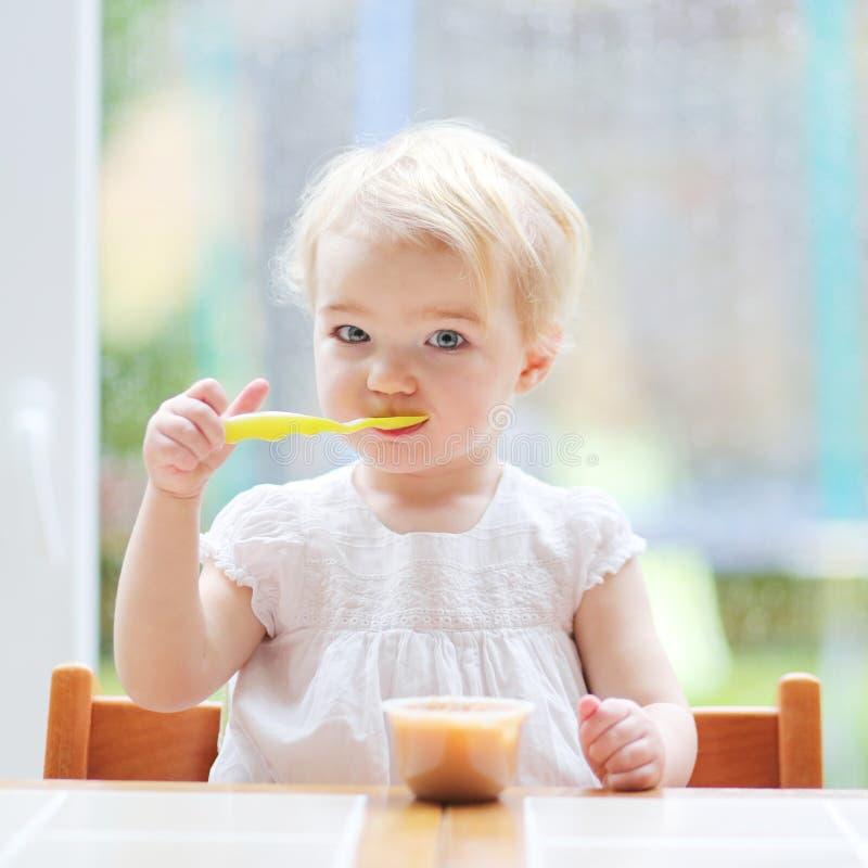 Κορίτσι μικρών παιδιών που τρώει τον πουρέ φρούτων στοκ εικόνα