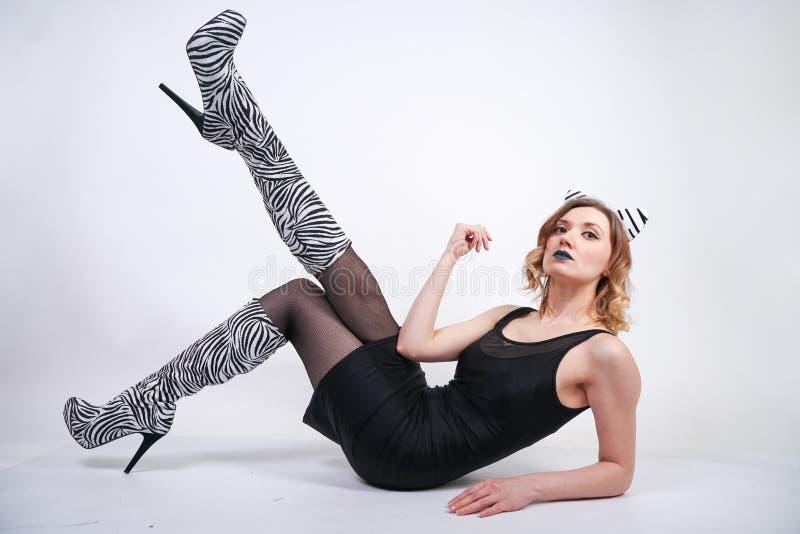 Κορίτσι μόδας που φορά το Μαύρο λίγο φόρεμα από το spandex με τις ζέβεις μπότες βελούδου με τα υψηλά τακούνια στο άσπρο υπόβαθρο  στοκ φωτογραφία