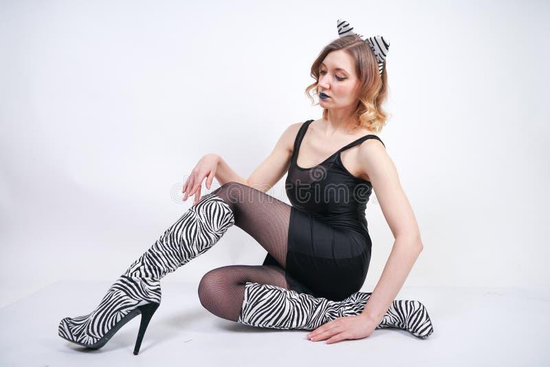 Κορίτσι μόδας που φορά το Μαύρο λίγο φόρεμα από το spandex με τις ζέβεις μπότες βελούδου με τα υψηλά τακούνια στο άσπρο υπόβαθρο  στοκ φωτογραφία με δικαίωμα ελεύθερης χρήσης