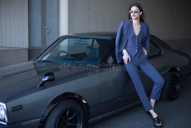 Κορίτσι μόδας που στέκεται δίπλα σε ένα αναδρομικό σπορ αυτοκίνητο στον ήλιο Μοντέρνη γυναίκα σε ένα γκρίζο κοστούμι που περιμένε στοκ φωτογραφίες