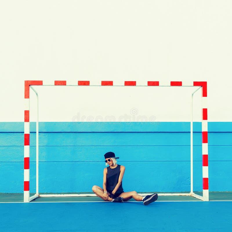 Κορίτσι μόδας στα μοντέρνα ενδύματα στο αγωνιστικό χώρο ποδοσφαίρου στοκ φωτογραφίες