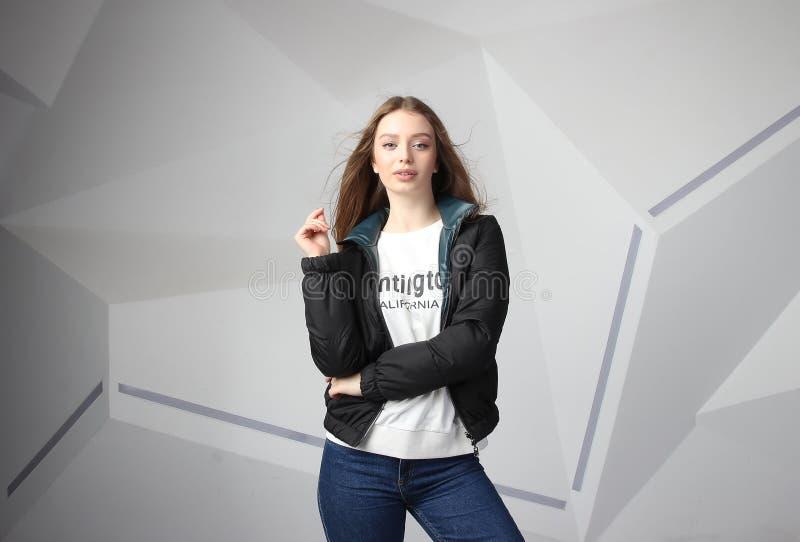 Κορίτσι νέων κοριτσιών που φορά το σακάκι με την περιοχή για το λογότυπό σας, πρότυπο των λευκών γυναικών hoodie στοκ εικόνες