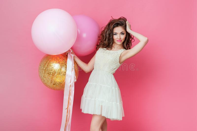 Κορίτσι ομορφιάς με τα ζωηρόχρωμα μπαλόνια αέρα που γελά πέρα από το ρόδινο υπόβαθρο Όμορφη ευτυχής νέα γυναίκα στο κόμμα διακοπώ στοκ εικόνες