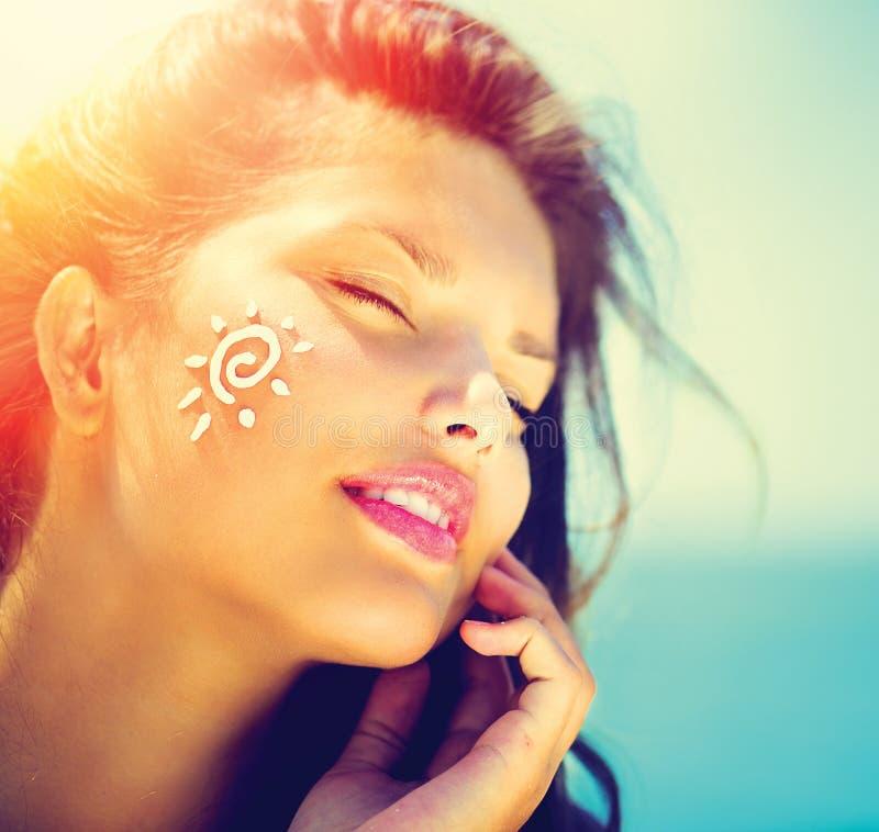 Κορίτσι ομορφιάς που εφαρμόζει την κρέμα Suntan στοκ εικόνα