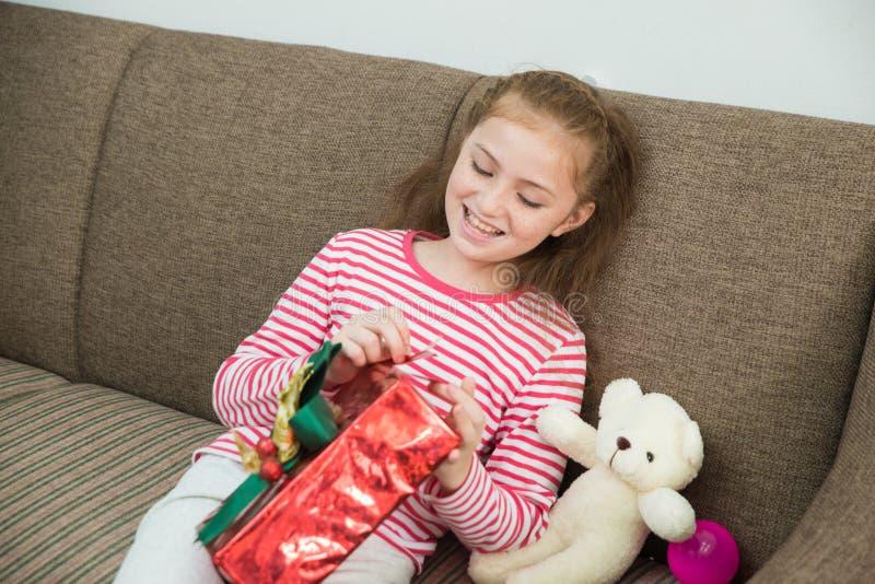 Κορίτσι παιδιών που κρατά ένα δώρο διαθέσιμο και κιβώτιο δώρων ανοίγματος το κόκκινο στοκ εικόνες με δικαίωμα ελεύθερης χρήσης