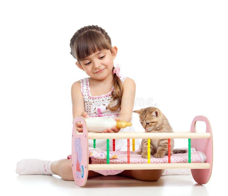 Κορίτσι παιδιών που ταΐζει και γάτα γατακιών παιχνιδιού στοκ φωτογραφίες