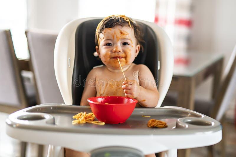 Κορίτσι παιδιών, που τρώει τα μακαρόνια για το μεσημεριανό γεύμα και που κάνει να βρωμίσει στο σπίτι στην κουζίνα στοκ εικόνες
