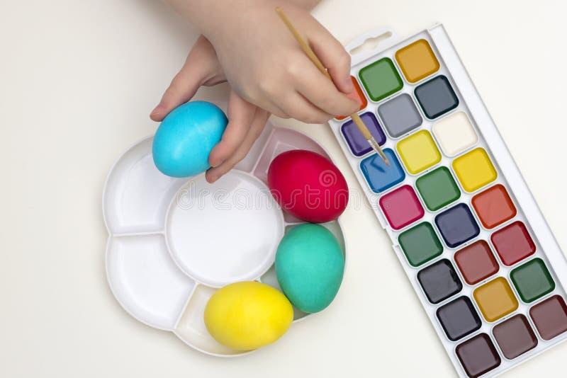 Κορίτσι παιδιών Lttle που χρωματίζει τα αυγά Πάσχας με τα διάφορα χρώματα στοκ εικόνες