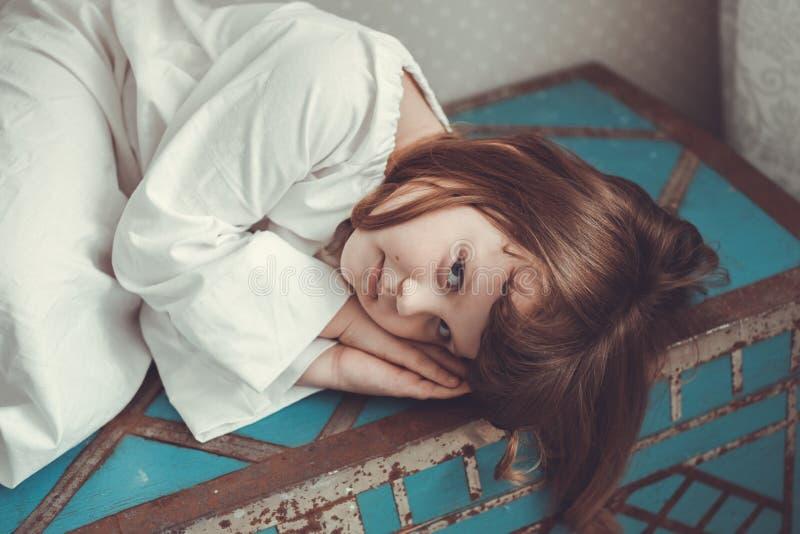 Κορίτσι παιδιών στο νυχτικό αναδρομικό στον μπλε παλαιό κορμό στοκ φωτογραφία με δικαίωμα ελεύθερης χρήσης