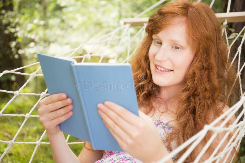 Κορίτσι πιπεροριζών που διαβάζει ένα βιβλίο σε μια αιώρα στοκ φωτογραφίες