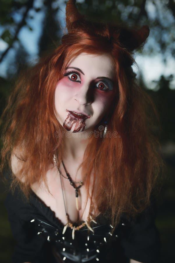 Κορίτσι πορτρέτου με την κόκκινη τρίχα και αιματηρό βαμπίρ προσώπου, δολοφόνος, ψυχο, θέμα αποκριών, αιματηρή γυναίκα στοκ εικόνα