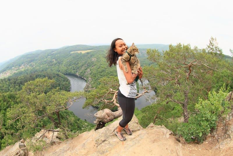 Κορίτσι που αγκαλιάζει τη γάτα στην άποψη σχετικά με τον ποταμό Vltava - Vyhlidka Maj στοκ φωτογραφία