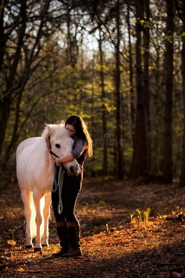 Κορίτσι που αγκαλιάζει το άσπρο άλογο στα ξύλα στοκ φωτογραφία