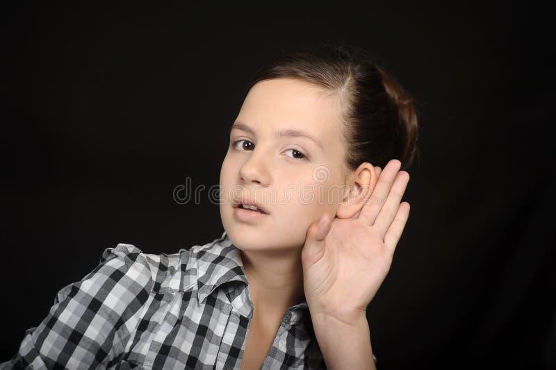 Κορίτσι που ακούει με το χέρι της σε ένα αυτί στοκ εικόνες
