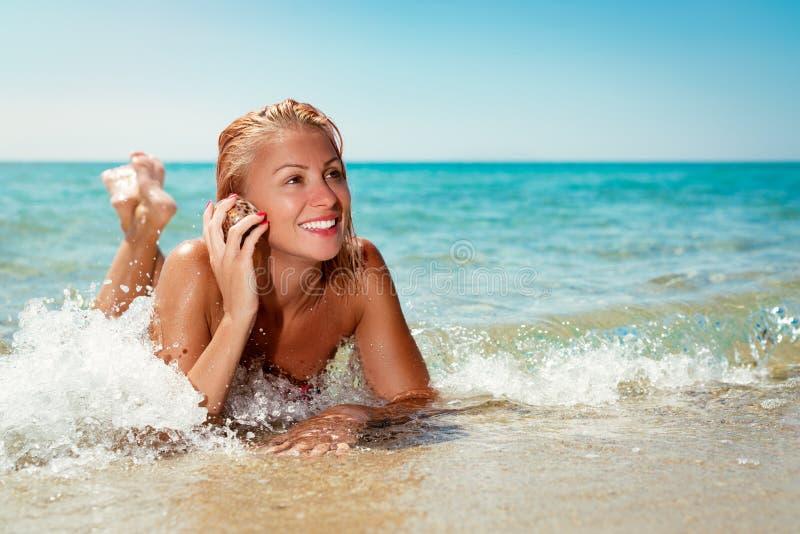 Κορίτσι που ακούει τη θάλασσα στοκ εικόνα