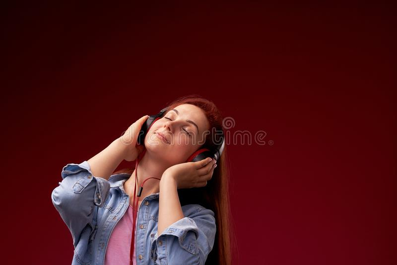 Κορίτσι που ακούει τη μουσική στα ακουστικά κοκκινομάλλες νέο όμορφο κορίτσι στα τζιν και ευτυχές χαμόγελο μπλουζών στα ακουστικά στοκ φωτογραφία με δικαίωμα ελεύθερης χρήσης