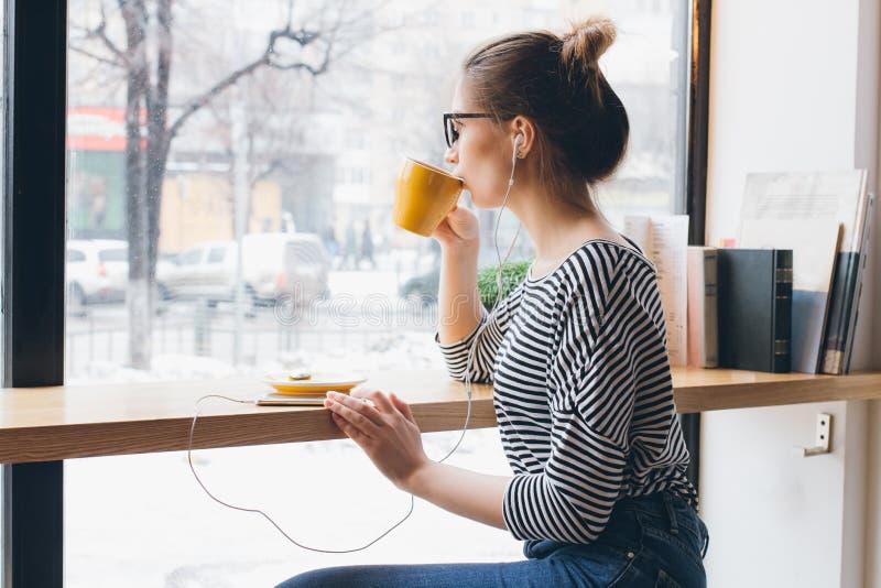 Κορίτσι που ακούει τη μουσική στον καφέ σας smartphone και κατανάλωσης στοκ εικόνα με δικαίωμα ελεύθερης χρήσης