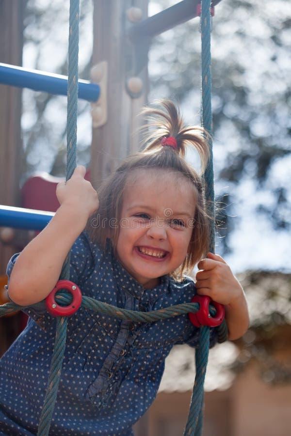Κορίτσι που αναπτύσσει την επιδεξιότητα στην παιδική χαρά στοκ φωτογραφίες