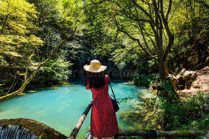 Κορίτσι που απολαμβάνει την ημέρα υπαίθρια στο φυσικό φρεάτιο νερού στοκ εικόνες