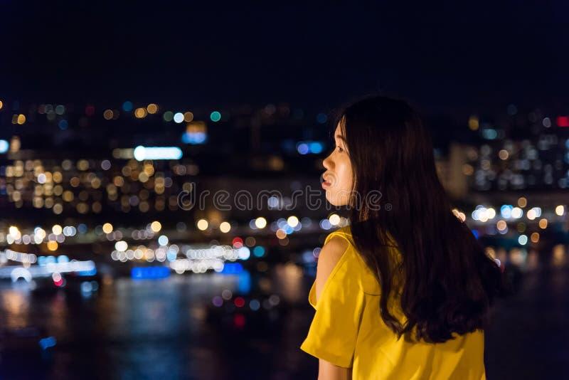 Κορίτσι που απολαμβάνει τη θέα πόλεων νύχτας άνωθεν στοκ εικόνα