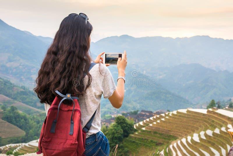 Κορίτσι που απολαμβάνει το ηλιοβασίλεμα στο terraced τομέα ρυζιού σε Longji, Κίνα στοκ φωτογραφία