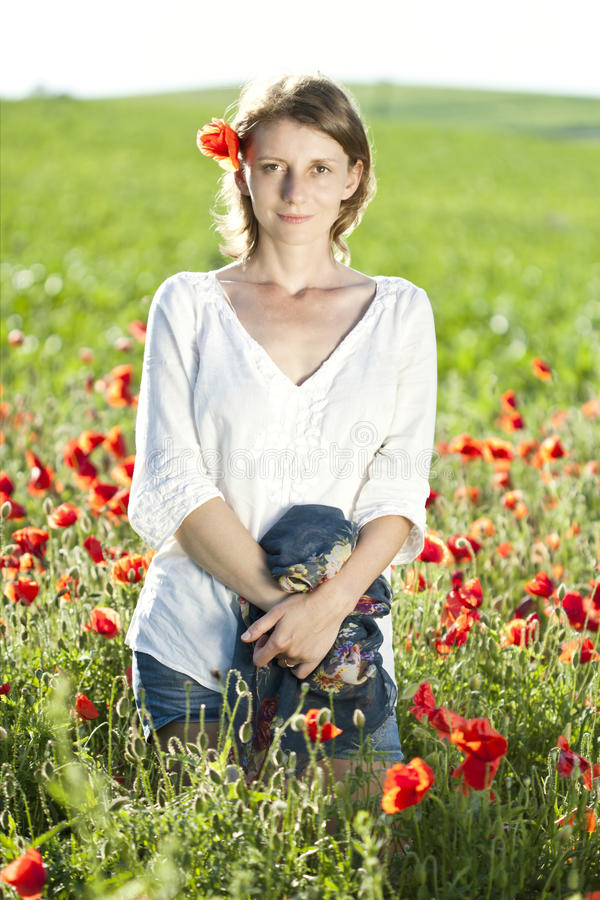 Κορίτσι που απολαμβάνει το καλοκαίρι σε έναν τομέα παπαρουνών στοκ εικόνα