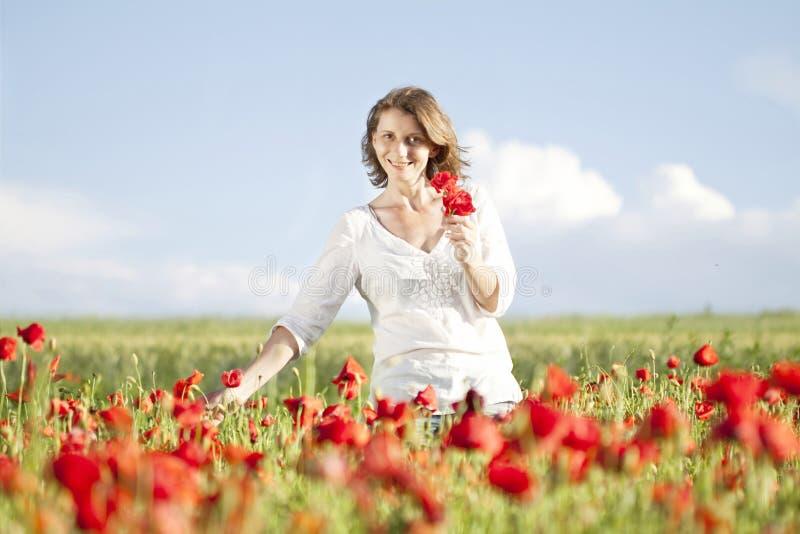 Κορίτσι που απολαμβάνει το καλοκαίρι σε έναν τομέα παπαρουνών στοκ εικόνες