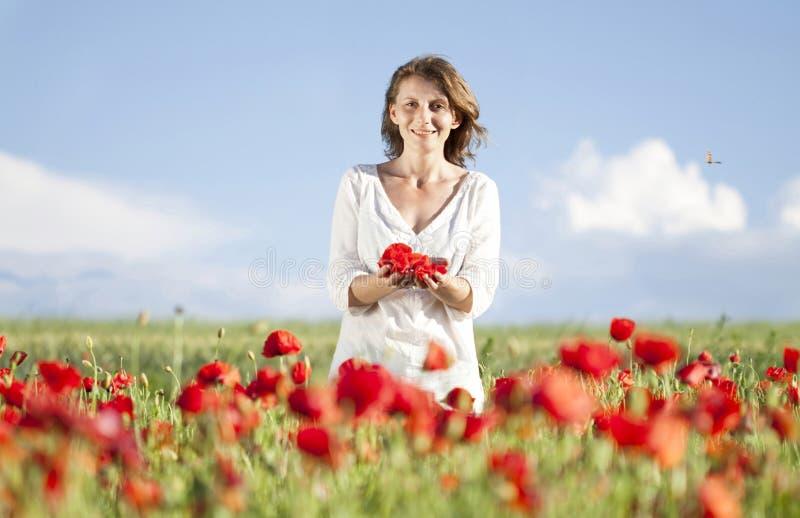 Κορίτσι που απολαμβάνει το καλοκαίρι σε έναν τομέα παπαρουνών στοκ εικόνα με δικαίωμα ελεύθερης χρήσης