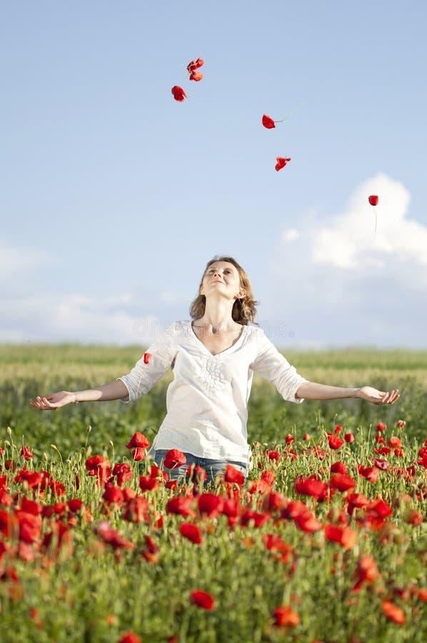 Κορίτσι που απολαμβάνει το καλοκαίρι σε έναν τομέα παπαρουνών στοκ φωτογραφία