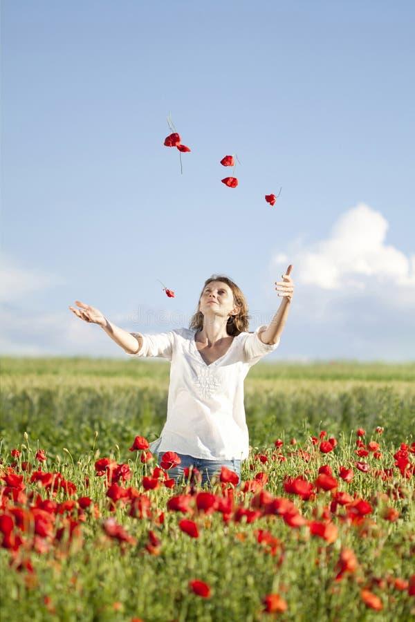 Κορίτσι που απολαμβάνει το καλοκαίρι σε έναν τομέα παπαρουνών στοκ φωτογραφία με δικαίωμα ελεύθερης χρήσης